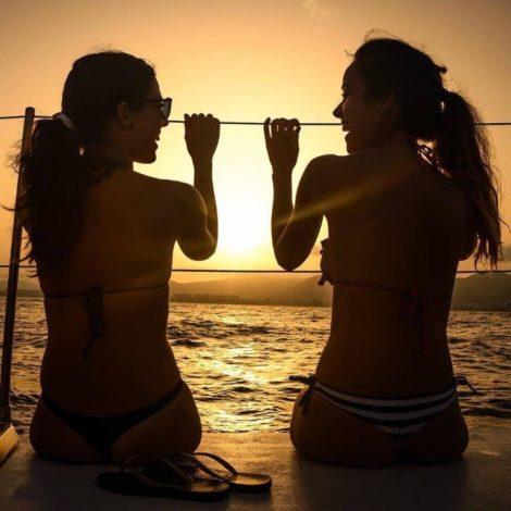 Two girls having fun on a catamaran rent in Ibiza